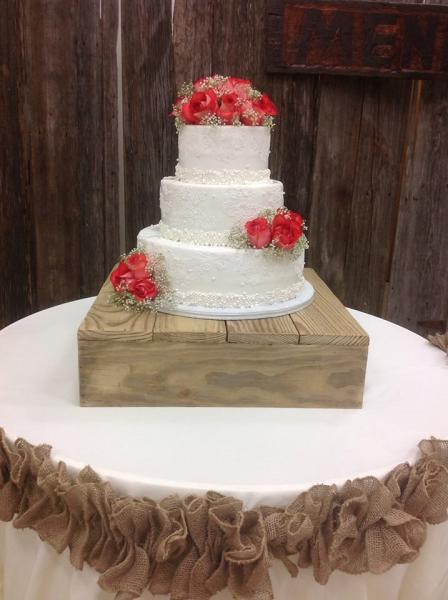 A 3 tier white wedding cake with fresh roses.