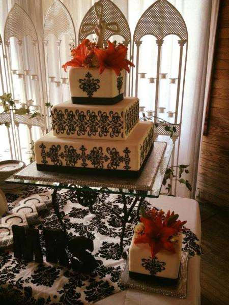 [Image: An elegant black and white wedding cake with lilies.]