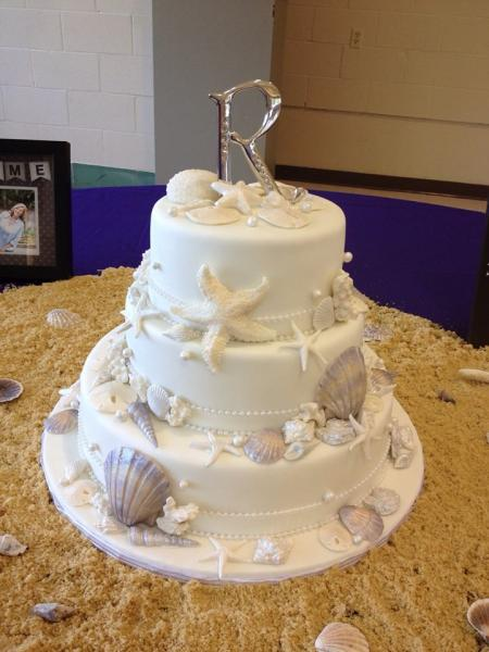 [Image: A seashell themed wedding cake.]
