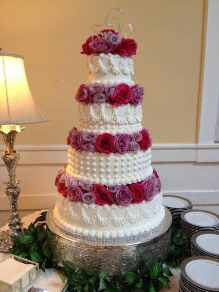 [Image: A 4 tier wedding cake with various designs on each tier as well as purple and pink flowers.]