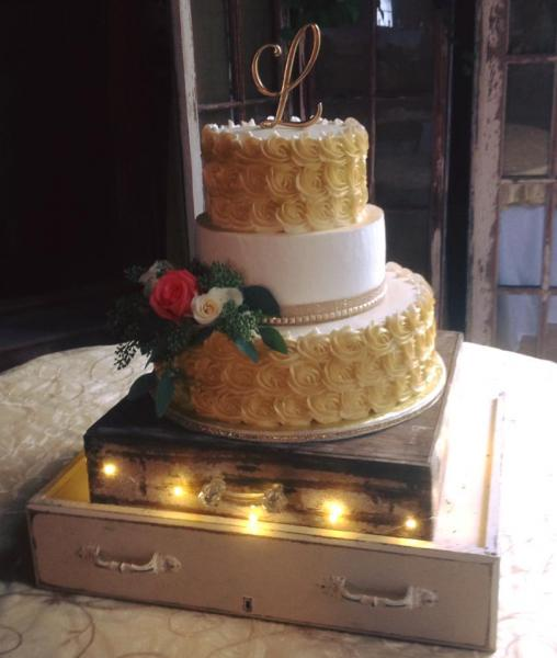 [Image: A 3 tier gold and white wedding cake.]