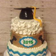A 3 tiered graduation cake with various prints on each tier and a graduation cap as the cake topper.