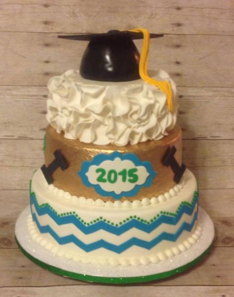 [Image: A 3 tiered graduation cake with various prints on each tier and a graduation cap as the cake topper.]