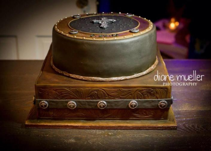 This is a beautiful golden brown cake etched with cowboy-inspired decorations. ]