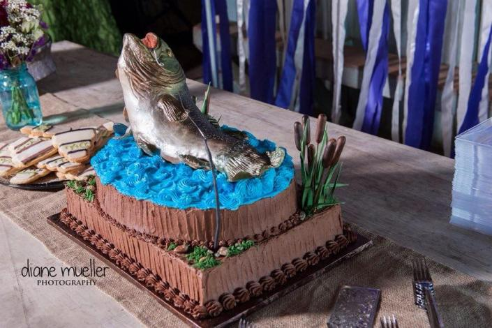 [Image: This realistic display of a fish leaping from blue water frosting is perfect for anyone who loved the outdoors!]