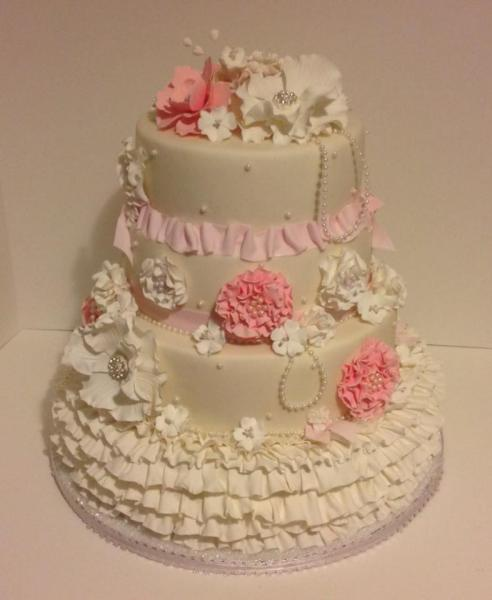 [Image: A gorgeous pink and ivory wedding cake with floral decor and beading.]
