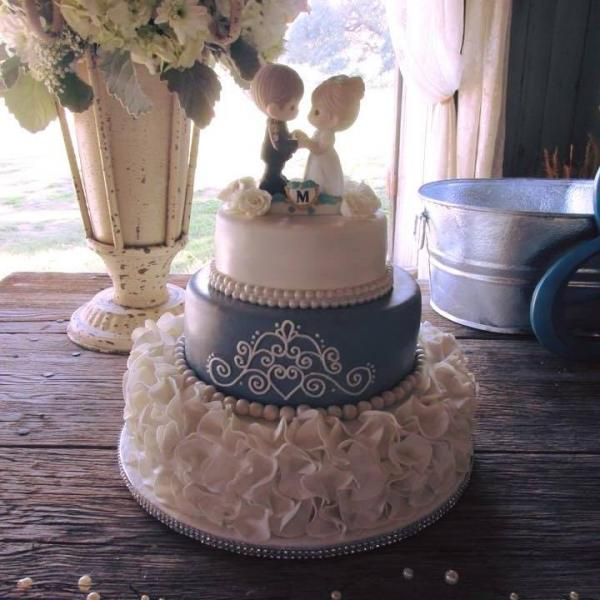 [Image: An adorable wedding cake with a Precious Moments topper.]