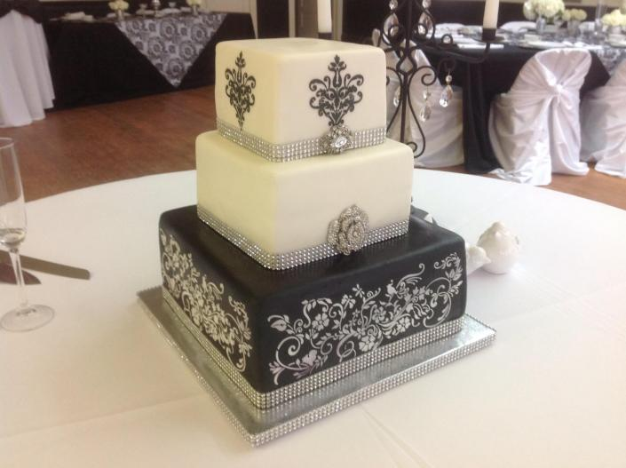 [Image: An elegant 3 tier black and white wedding cake.]