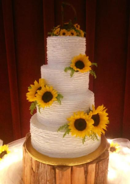 [Image: A beautiful 4 tier wedding cake with sunflowers.]