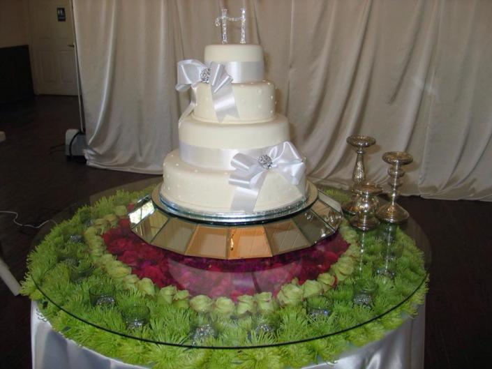[Image: A beautiful wedding cake with white ribbon.]