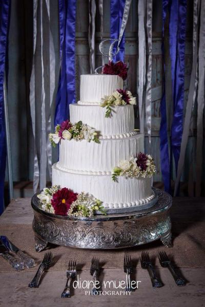 A stunning 4 tier wedding cake with fresh flowers.]