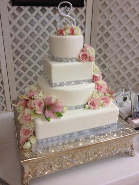 [Image: A 4 tier wedding cake with various shapes as well as crystal embellishment.]