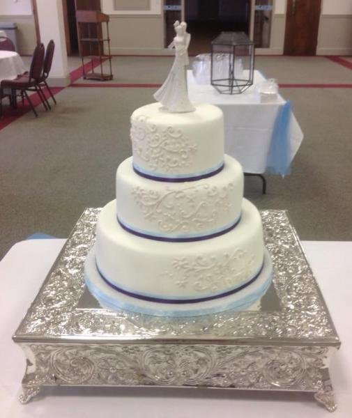 [Image: A 3 tier wedding cake with a subtle hint of blue.]