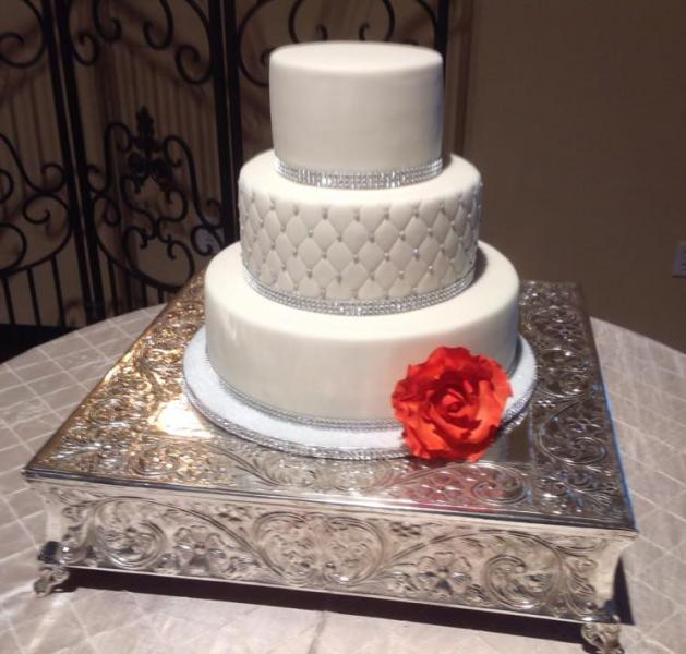[Image: A beautiful wedding cake with an orange rose.]