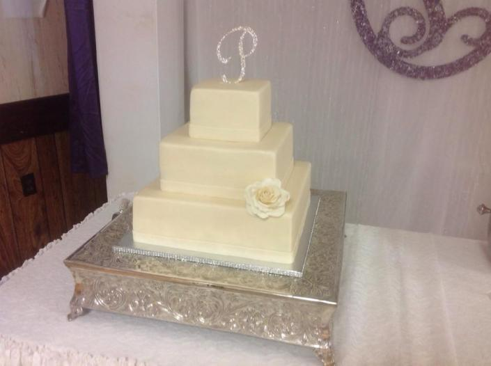 [Image: An all white wedding cake.]